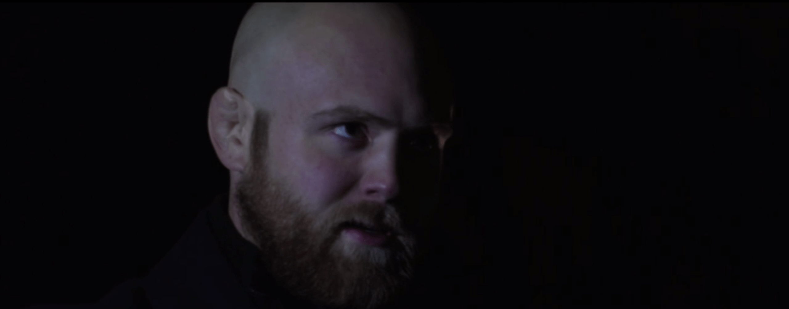 Scowling bald man with a beard
