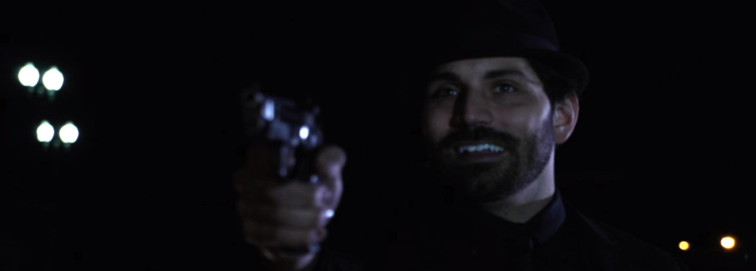 A fedora-wearing man pointing a gun