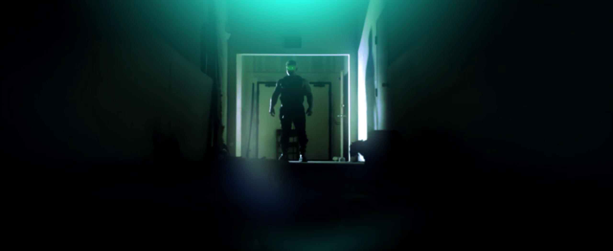 Zombie Duke Nukem with glowing eyes walking down a dark hallway