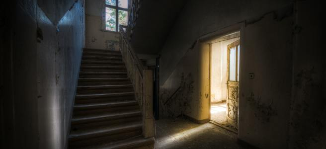 A dark hallway in a derelict house. Photo by Nathan Wright on Unsplash